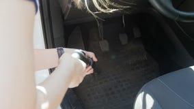 V?deo de la c?mara lenta de la mujer joven usando la aspiradora para limpiar su coche interior del polvo y de la suciedad Limpiez almacen de video
