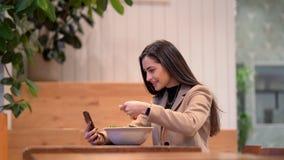 V?deo de la muchacha que come una ensalada y que usa el tel?fono celular almacen de metraje de vídeo