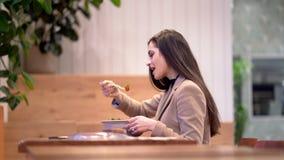V?deo de la muchacha que come una ensalada y que usa el tel?fono celular almacen de video