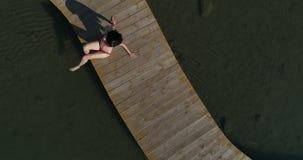 V?deo de la mujer en traje de ba?o que toma el sol en el embarcadero Relajaci?n femenina el vacaciones metrajes
