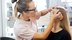 V?deo de movimento lento do close up do maquilhador profissional que aplica cosm?ticos e que prepara o modelo f?mea novo para filme