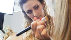 v?deo do close up 4k do maquilhador profissional que aplica o r?mel e que pinta olhos e as testas dos modelos no profissional video estoque