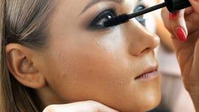 v?deo do close up 4k do maquilhador profissional que aplica o r?mel e que pinta olhos e as testas dos modelos no profissional filme