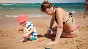 v?deo 4k de la madre joven con su hijo del ni?o que juega con el coche del juguete en la playa del mar Familia que se relaja dura almacen de metraje de vídeo