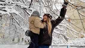 v?deo 4k de la madre joven que detiene a su hijo del ni?o y que sacude las ramas de ?rbol cubiertas con nieve Familia que se divi metrajes