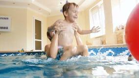 v?deo 4k de la madre joven sonriente feliz con 3 a?os de la nataci?n del ni?o peque?o y el jugar en piscina en el gimnasio metrajes