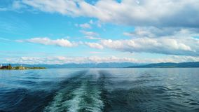 v?deo 4K de la nave en el lago de Constanza, Bodensee Vela del barco en el lago El agua es azul cristalino y detrás de ella se co almacen de video
