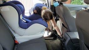 v?deo 4k de los asientos de carro de limpieza de la mujer joven del polvo y de la suciedad con el aspirador almacen de metraje de vídeo
