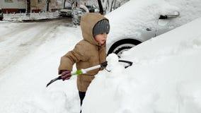 v?deo 4k de 3 a?os del ni?o peque?o que ayuda limpiando el coche cubierto en nieve despu?s de nevada metrajes