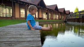 v?deo 4k del ni?o peque?o sonriente chererful que se sienta en el riverbank y que lleva a cabo pies en agua del peque?o canal en  almacen de metraje de vídeo