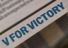 V för segertagline i tidning med blåa och djärva bokstäver Royaltyfria Bilder