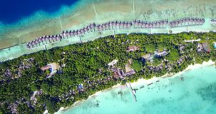V09494 five 5 star resort water bungalows in Maldives with drone aerial flying view on white sand beach on tropical. Five 5 star resort water bungalows in Royalty Free Stock Photo
