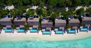 V09552 five 5 star resort water bungalows in Maldives with drone aerial flying view on white sand beach on tropical. Five 5 star resort water bungalows in Royalty Free Stock Photography