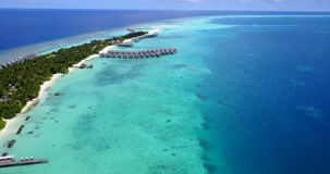 V09458 five 5 star resort water bungalows in Maldives with drone aerial flying view on white sand beach on tropical. Five 5 star resort water bungalows in Stock Photos