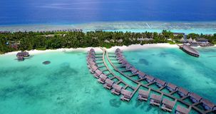 V09465 five 5 star resort water bungalows in Maldives with drone aerial flying view on white sand beach on tropical. Five 5 star resort water bungalows in Royalty Free Stock Images