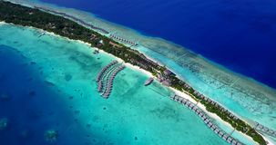 V09479 five 5 star resort water bungalows in Maldives with drone aerial flying view on white sand beach on tropical. Five 5 star resort water bungalows in Stock Photos