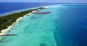 V09456 five 5 star resort water bungalows in Maldives with drone aerial flying view on white sand beach on tropical. Five 5 star resort water bungalows in Royalty Free Stock Photography