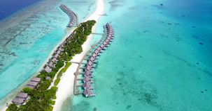 V09533 five 5 star resort water bungalows in Maldives with drone aerial flying view on white sand beach on tropical. Five 5 star resort water bungalows in Royalty Free Stock Photo