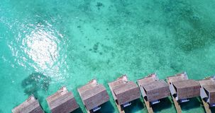 V09434 five 5 star resort water bungalows in Maldives with drone aerial flying view on white sand beach on tropical. Five 5 star resort water bungalows in Stock Photos