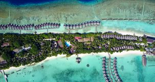 V09491 five 5 star resort water bungalows in Maldives with drone aerial flying view on white sand beach on tropical. Five 5 star resort water bungalows in Royalty Free Stock Images