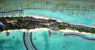 V09489 five 5 star resort water bungalows in Maldives with drone aerial flying view on white sand beach on tropical. Five 5 star resort water bungalows in Stock Image