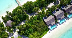 V09546 five 5 star resort water bungalows in Maldives with drone aerial flying view on white sand beach on tropical Stock Image