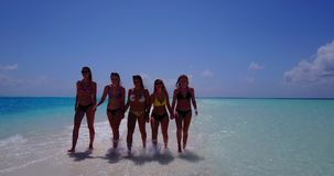 V13827 Five 5 walking beautiful young girls in bikini sunbathing with drone aerial flying view on white sand island Stock Image