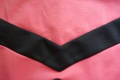 V-format band som sys till rosa tyg Royaltyfria Foton