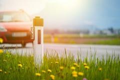 V?g i sommaren: reflektorstolpe, bilar, blommor och gr?nt gr?s sunbeam royaltyfri bild