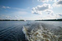 V?gen gjorde fartyget p? floden En svans av spårar av riverboaten på bärplansbåten på en yttersida av vattnet på royaltyfri bild