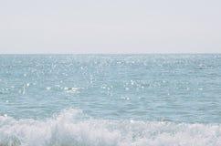 V?gorna av havet Ilskna blicken av solen i vattnet Den blåa bakgrunden av havet royaltyfri bild