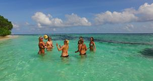 V12679 group of young beautiful girls playing beach ball and sunbathing in aqua blue clear sea water and sky. Group of young beautiful girls playing beach ball Stock Photos