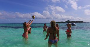 V12684 group of young beautiful girls playing beach ball and sunbathing in aqua blue clear sea water and sky. Group of young beautiful girls playing beach ball Royalty Free Stock Photo