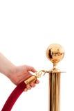 V.I.P somente!!! Mão que abre a corda vermelha Foto de Stock Royalty Free