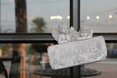V?lkommet tecken p? stenen mot exponeringsglasd?rr av restaurangen royaltyfria foton