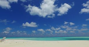 V07077 Maldives white sandy beach clouds on sunny tropical paradise island with aqua blue sky sea ocean 4k. Maldives white sandy beach clouds on sunny tropical Stock Images