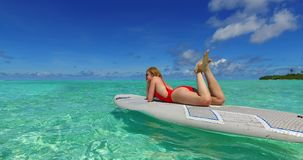 V07349 Maldives white sandy beach 2 people young couple man woman paddleboard rowing on sunny tropical paradise island. Maldives white sandy beach 2 people young stock footage