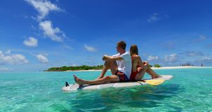 V07300 Maldives white sandy beach 2 people young couple man woman paddleboard rowing on sunny tropical paradise island Stock Photo