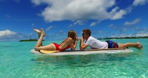 V07317 Maldives white sandy beach 2 people young couple man woman paddleboard rowing on sunny tropical paradise island Royalty Free Stock Images