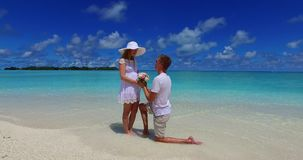 V07386 Maldives white sandy beach 2 people young couple man woman proposal engagement wedding marriage on sunny tropical Stock Photo