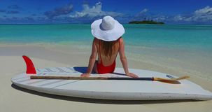 V07450 Maldives white sandy beach 2 people a young couple man woman sitting together on sunny tropical paradise island. Maldives white sandy beach 2 people a stock footage