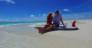 V07440 Maldives white sandy beach 2 people a young couple man woman sitting together on sunny tropical paradise island. Maldives white sandy beach 2 people a stock footage