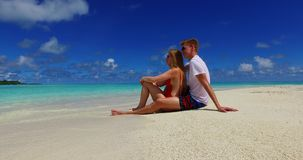 V07419 Maldives white sandy beach 2 people a young couple man woman sitting together on sunny tropical paradise island Stock Photos