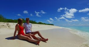 V07466 Maldives white sandy beach 2 people a young couple man woman sitting together on sunny tropical paradise island Stock Photo