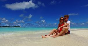 V07428 Maldives white sandy beach 2 people a young couple man woman sitting together on sunny tropical paradise island Stock Images