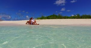 V07398 Maldives white sandy beach 2 people a young couple man woman sitting together on sunny tropical paradise island Royalty Free Stock Photography