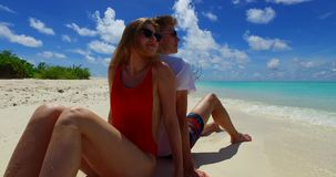 V07408 Maldives white sandy beach 2 people a young couple man woman sitting together on sunny tropical paradise island Stock Photos