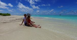 V07413 Maldives white sandy beach 2 people a young couple man woman sitting together on sunny tropical paradise island Stock Images