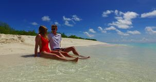 V07460 Maldives white sandy beach 2 people a young couple man woman sitting together on sunny tropical paradise island Stock Image