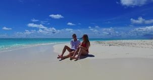 V07433 Maldives white sandy beach 2 people a young couple man woman sitting together on sunny tropical paradise island Stock Images